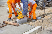 Workers Using Machine To Align And Set The Concrete Curbs