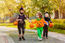 Three Running Kid With A Basket For Sweets Wearing Face Mask On Halloween Holiday