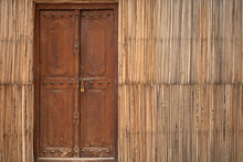 An Old Wooden Closed Door In Straw Wall With Copy Space