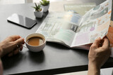 Man with cup of coffee reading magazine in office