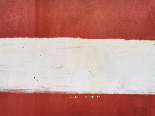 Texture Of Old Painted Rusty Red Wall Or Garage Door With Peeling And Cracked Paint And Corrosion And White Stripe