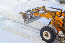 A Bulldozer With A Bucket Clears Snow From The Road In Winter After A Snowfall
