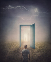 Teleportation Doors Concept. Rear View Of A Person Standing In Front Of A Doorway In The Land, As Seen In The Mirror Like A Portal To Another World. Magical And Surreal Scene With Spooky Lightnings