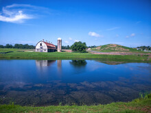 Abandoned Farm With An Old Silo Tower Reflected In A Pond