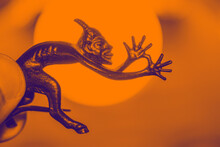 A Small Metal Sculpture Of The Devil With A Tail Showing His Tongue