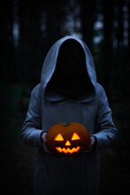 Mysterious Figure In Monk Or Wizard Costume Holding Carved Jack-o-lantern Pumpkin Head. Halloween Concept.