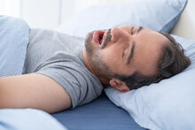 Man Snoring Loudly In His Bed While Sleeping