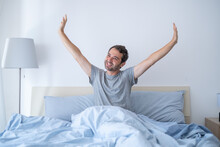 Man Portrait Stretching In The Morning In His Bed