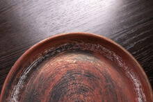 Used Earthenware Plate (pot Tray). Selective Focus. Scuff Marks. Dark Wood Textured Background