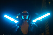 Hot Party Girl In Sunglasses Leaning On Brick Wall In Night Street. Close-up Portrait Of Caucasian Young Brunette Woman Holding Match In Her Teeth In Neon Blue City Light