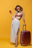 full length of happy young woman in ruffle bikini top and sun hat standing near luggage and holding cocktail on yellow.