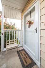 Front Entrance Of A House With Glass Storm Door And Home Sweet Home Doormat