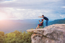 Tourist Couple On Top Of The Mountain And Taking A Picture Of Valley. Sut Phaendin Cliff, Chaiyaphum, Thailand