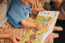 Cute Little Girl Pointing At Pictures In Book. Toddler Sitting On Her Mother Laps And Reading Book. Family At Home, Child Development Concept