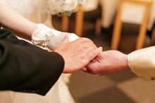 結婚式での花嫁と花婿と父の握手