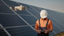 Industrial Expert Wearing Helmet And Controlling Drone In Photovoltaic Solar Power Plant. Solar Panel Array Installation. Technologies And Ecology. New Technologies