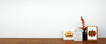 Halloween Decor On A Wood Shelf. Shabby Chic Wood Signs, Calendar And Orange Branches Against A White Wall Banner. Copy Space.