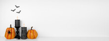 Halloween Shelf Display With Pumpkins, Black Candles And Spiders Against A White Wall With Bats. White Shelf. Banner With Copy Space.