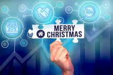 Text Sign Showing Merry Christmas. Concept Meaning Annual Tradition To Celebrate The Birth Of Jesus Christ Hand Holding Jigsaw Puzzle Piece Unlocking New Futuristic Technologies.