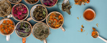Assortment Of Dried Relaxing Tea Herbs In Colourful Cups On Blue Background With Honey Close Up. Calendula, Mint, Anise Hyssop, Monarda Didyma, Wormwood, Sage Leaves.