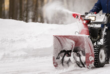 A Man With A Red Snow-covered Snow Blower Clears The Area From Snow. Clearing The Area From Snowfall.