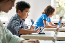 Focused Asian School Boy Using Digital Tablet At Class In Classroom. Attentive Junior School Student Learning Online Virtual Education Digital Program App Tech During Stem Computer Science Lesson.