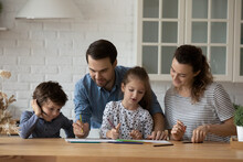 Happy Couple Teaching Sibling Kids To Draw With Color Pencils. Parents, Preschooler Son And Daughter Standing At Table Together, Enjoying Craft Activities, Developing Creative Artistic Skills