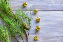 Green Branch Of Pine Tree And Yellow Christmas Balls On Rustic Table. Christmas Concepts. Free Space For Text