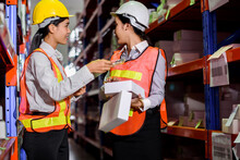 Engineer Warehouse Woman Wearing A Hardhat Standing Cargo At Goods Warehouse And Check For Control Loading From Cargo Freight Ship For Import And Export By Report On Tablet. Teamwork Concept