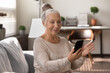 Leinwandbild Motiv Happy elderly grey haired lady using smartphone at home, making video call, talking to family, relatives online. Senior patient consulting doctor at virtual meeting on mobile phone, smiling at screen