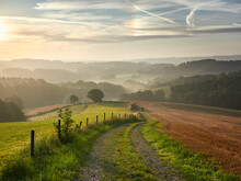 Rural Landscape In The German City Of Velbert At Sunrise In The Bergisches Land Region. A Dirt Road In The Foreground And Hazy Woods In The Background