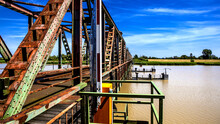 Old Rusty Girder Bridge Over A Dirty River Under The Sunlight