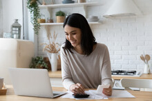 Happy Young Asian Korean Woman Managing Household Budget, Calculating Bills, Paying Online For Services Taxes In E-banking Application, Planning Future Investment, Feeling Satisfied With Enough Money.