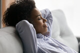 Peace of mind. Side view of happy serene millennial african american lady relax recline on comfortable sofa with closed eyes. Satisfied peaceful young mixed race female meditate breath deep sleep nap