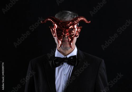 Fototapeta businessman in devil mask on black background