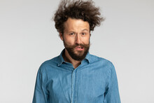 Young Casual Man In Denim Shirt With Curly Hair Making Funny Faces