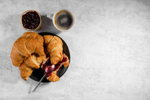Fresh French Croissant With Cherry Jam On Grey Plate And Cap Of Fresh Coffee On Gray Background, One Teaspoon Spreads Jam On Croissant, Delicious Sweet Breakfast With Pastries Top View, Copy Space