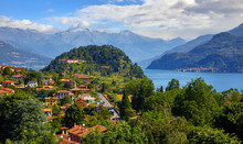 Bellagio Village At Lake Como, Italy. Panoramic View At Hill With Park And Antique City Among Mountains And Green Forests. Summer Picturesque Landscape With Water, Waves And Blue Sky With Clouds.
