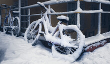 Snow Covered Bicycle Between Houses