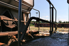 Mechanisms Of An Old And Rusty Wagon And A Train Station In The Background
