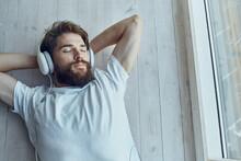 Man In White T-shirt Lying Near The Window Wearing Headphones Technology