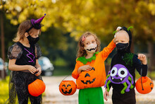 Three Kid With A Basket For Sweets Making Grimaces Wearing Face Mask On Halloween Holiday