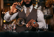 Faceless Black Bartender Sprinkling Glass With Yellow Powder At Work