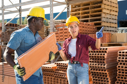 Photo Young girl manager working in a building materials store shows a male colleague