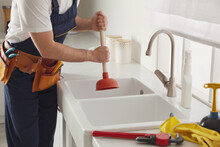Plumber Using Plunger To Unclog Sink Drain In Kitchen, Closeup