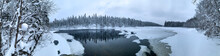 Panorama Of An Ice-covered River Among A Frozen Taiga Forest In A Harsh Winter