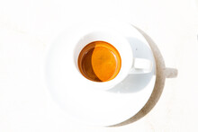 Round White Coffee Cup On White Surface. High Contrast Picture. Traditional Italian Ristretto In Bright Summer Day. Top View Geometrical Round Composition. Hot Caffeine Beverage In A Small Cup.