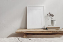 Vertical White Picture Frame Mockup. Vintage Wooden Bench, Table. Cup With Dry Grass On Pile Of Books. White Wall Background. Scandinavian Interior, Neutral Color Palette. Selective Focus. Art Display