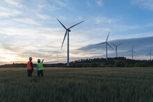 Unrecognized Engineers Wearing Safety Helmets Working In Wind Turbine Farm During The Evening.