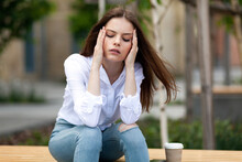 The Girl Has A Headache. A Student Sits On A Bench In The Park. Tired Office Worker.drinks Coffee.